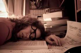 An exhausted woman falls asleep at her desk, amidst paper and notebooks.