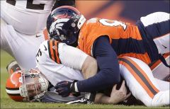 Cleveland Browns quarterback Brandon Weeden, left, is sacked by Broncos defensive end Elvis Dumervil.