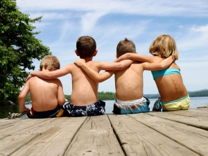 Four kids who are friends, sit on a dock with their arms around each others'' shoulders.