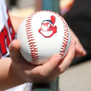 Child's hand holding a baseball with the Cleveland Indians logo, waiting for a player to sign it