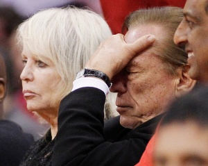 Los Angeles Clippers owner Donald Sterling (R) puts his hand over his face as he sits courtside with his wife Shelly (L) while the Clippers trail the Chicago Bulls in the second half of their NBA basketball game in Los Angeles December 30, 2011.