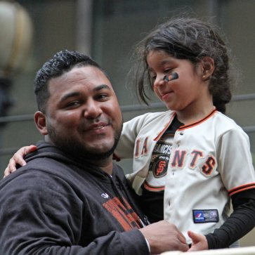 San Francisco Giants reliever Jean Machi and his daughter ride in the World Series victory parade on October 31, 2014.