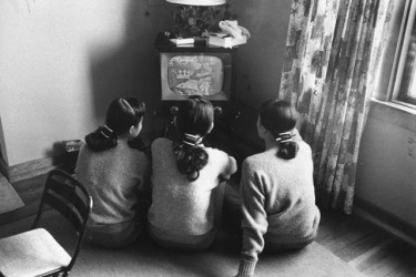 Black and white photo of three women watching a small television, probably 1950 - 1960.