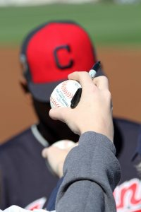 Image of hands holding out baseballs for Cleveland Indians players to sign, before a spring training game in 2017